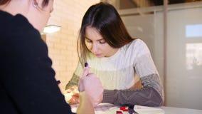 La muchacha elige el color y la textura de clavos en el salón de belleza profesional de la manicura, resbalador almacen de metraje de vídeo