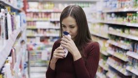 La muchacha elige el gel de la ducha y lo huele en el departamento en el supermercado, aversión de los cosméticos de la emoción almacen de video