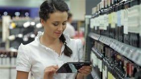 La muchacha elige el vino con una tableta almacen de metraje de vídeo