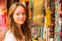 La muchacha elige la decoración en el mercado en Asia Imagenes de archivo
