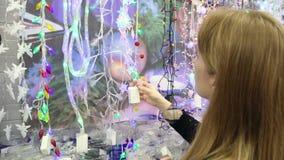 La muchacha elige la guirnalda del árbol de navidad almacen de metraje de vídeo