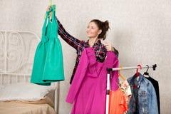 La muchacha elige los vestidos imagen de archivo