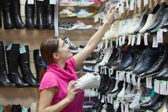La muchacha elige los zapatos en el departamento de zapatos Foto de archivo libre de regalías
