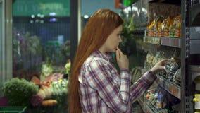La muchacha elige nueces en el hipermercado almacen de metraje de vídeo