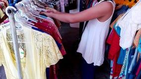 La muchacha elige la ropa en la tienda