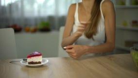 La muchacha elige la torta en vez de la ensalada, abandona el agotar de la dieta, azúcar para la energía del cuerpo almacen de video