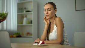 La muchacha elige la torta en vez de la ensalada, tentación de parar adietar, comida malsana almacen de metraje de vídeo
