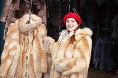 La muchacha elige un abrigo de pieles fotos de archivo libres de regalías
