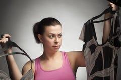 La muchacha elige un traje de vestido Fotografía de archivo libre de regalías