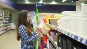 La muchacha elige una maceta en el supermercado almacen de video