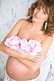 La muchacha embarazada atractiva cerca de la pared de ladrillo cierra el pecho con las flores Imagenes de archivo