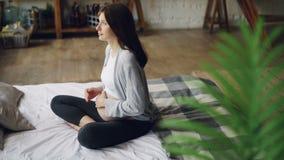 La muchacha embarazada cariñosa está frotando ligeramente su topetón del bebé que se sienta en cama en dormitorio en casa y que g almacen de metraje de vídeo