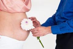 La muchacha embarazada con el hombre y la flor Fotos de archivo libres de regalías
