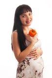 La muchacha embarazada de los jóvenes está comiendo la pimienta. Foto de archivo