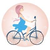 La muchacha embarazada en vestido azul monta una bicicleta Fotografía de archivo libre de regalías