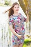 La muchacha embarazada es árbol cercano derecho Imagen de archivo