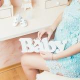 La muchacha embarazada está deteniendo al bebé de madera de las letras La mujer embarazada en un vestido azul se sienta cerca de  Fotografía de archivo libre de regalías