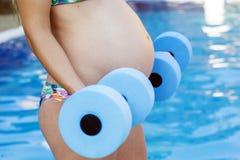 La muchacha embarazada está haciendo deporte con pesas de gimnasia cerca Imágenes de archivo libres de regalías