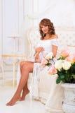 La muchacha embarazada hermosa en un vestido blanco del cordón se sienta en una cama Fotografía de archivo libre de regalías