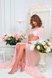 La muchacha embarazada hermosa se sienta en silla y mira el vientre con amor Fotografía de archivo