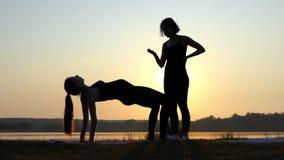 La muchacha embarazada practica yoga con su coche en un banco del lago en la puesta del sol almacen de video