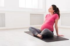 La muchacha embarazada que se sienta en actitud del loto, acaricia su vientre Fotos de archivo