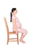 La muchacha embarazada se sienta en sideview de la silla Fotografía de archivo