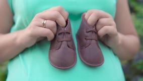 La muchacha embarazada se sostiene en sus zapatos del ` s de los niños de las manos en el fondo de arbustos verdes almacen de video