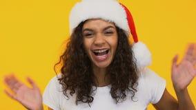 La muchacha emocionada en el sombrero de Papá Noel salta, saludando feliz Navidad, humor festivo metrajes