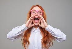 La muchacha emocional del pelirrojo que lleva a cabo las manos acerca a la boca y al sho Imagen de archivo