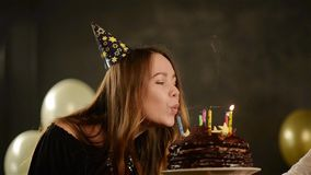 La muchacha emocional feliz sopla hacia fuera velas durante la celebración su cumpleaños y aplaude Ciérrese encima del retrato de almacen de metraje de vídeo