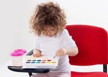 La muchacha emocional que se sienta en sillas rojas Imágenes de archivo libres de regalías