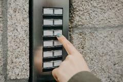 La muchacha empuja el botón del doorphone o llama el intercomunicador fotos de archivo