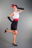 La muchacha en actitudes largas de los guantes del vestido Negro-blanco de Red Hat sonríe Imagen de archivo libre de regalías