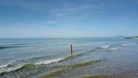 La muchacha en agua ata el pelo contra el cielo que se combina con el mar