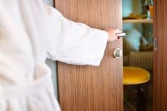 La muchacha en la albornoz casera blanca abre la puerta fotografía de archivo libre de regalías