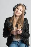 La muchacha en auriculares atados con alambre es música que escucha de su teléfono Imagen de archivo libre de regalías