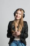 La muchacha en auriculares atados con alambre es música que escucha de su teléfono Imagen de archivo