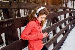 La muchacha en auriculares escucha la música en parque del invierno Imágenes de archivo libres de regalías
