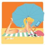 La muchacha en bikini en la estera de la playa trata en smartphone Fotos de archivo