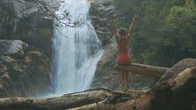 La muchacha en bikini se sienta en tronco de árbol hace ejercicios