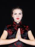 La muchacha en blusa de seda japonesa pone las manos antes de pecho fotografía de archivo