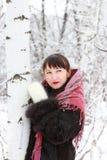 La muchacha en bosque del invierno mira lejos Imagen de archivo