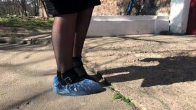 La muchacha en botas negras pone sus cubiertas azules del zapato del hospital de las piernas almacen de metraje de vídeo
