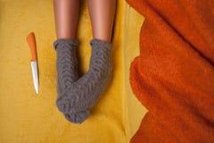 La muchacha en calcetines hechos punto está mintiendo en el sofá con el cuchillo Imágenes de archivo libres de regalías