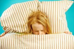 La muchacha en cama con miedo la cerró los ojos, referidos, ve las pesadillas, asustadas salir de debajo la manta, visión superio imágenes de archivo libres de regalías