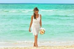 La muchacha en caminar blanco en la playa Fotos de archivo libres de regalías