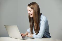 La muchacha en camisa clásica se sienta en el ordenador portátil y ríe Imagen de archivo