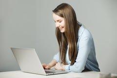La muchacha en camisa clásica se sienta en el ordenador portátil y la sonrisa Imágenes de archivo libres de regalías