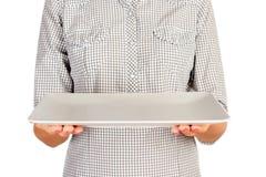 La muchacha en la camisa de tela escocesa está sosteniendo una placa mate rectangular vacía delante de ella plato vacío del contr imagen de archivo libre de regalías